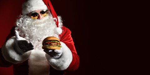 Happy Santa Claus in stylish sunglasses offer tasty burger sandwich hamburger in hand. New year