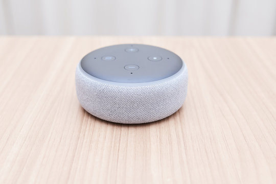 third generation amazon echo dot, white, low view, poorly focused, on a light wooden table