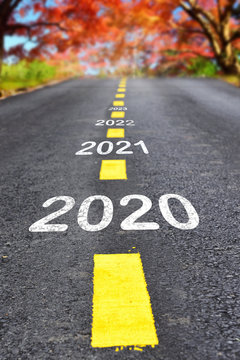 New year 2020 to 2023 on asphalt road surface with autumn season background