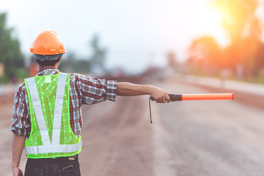 Worker with light stick on road construction background