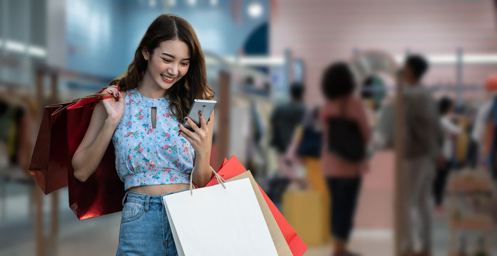 Shopping woman holding shopping bags looking on smartphone in shopping mall background.