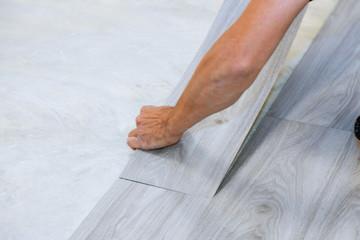 Worker installing new vinyl tile floor laminate wood texture floor with new home improvement