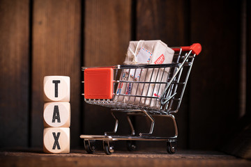 "shopping cart and cubes with the word ""tax"" on wooden background"