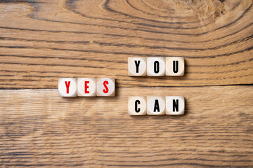 "wooden blocks with message ""yes, you can"" on wooden background"