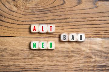 """Würfel mit Aufschrift """"Alt- und Neubau"""" auf Holzuntergrund"""