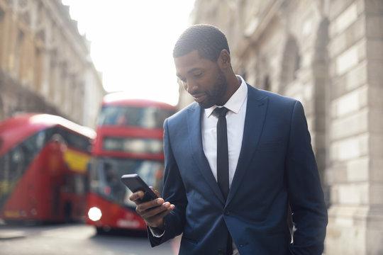 Elegant businessman walking in the street, checking his phone
