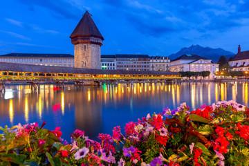 Lucerne. The famous Chapel, Kapellbrucke bridge at dawn in night lighting.