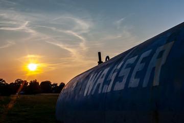 Wassertank auf einer Weide im Sonnenuntergang