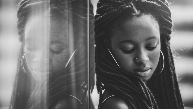 Portrait of a charming African girl with long braids leaning against the mirror which fully reflects her; dazzling young Guinean woman with braided hair is leaning on a glass reflecting wall outdoors