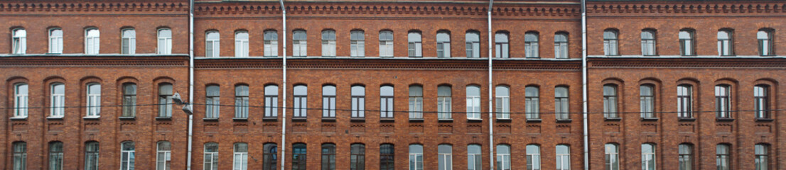 Panorama of the facade of an old brick apartment building as a background
