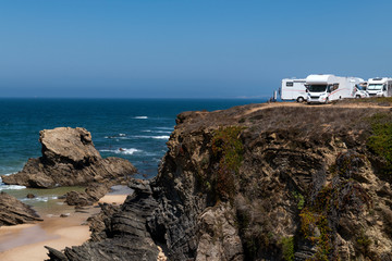 Campers parked on a cliff near the village of Porto Covo, in the Costa Vicentina Natural Park in Portugal; Concept for road trip in Portugal and summer vacations