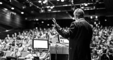 Speaker giving a talk on corporate business conference. Unrecognizable people in audience at conference hall. Business and Entrepreneurship event. Black and white image.