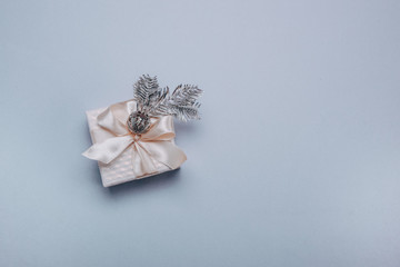 Christmas composition.Small gift box with Christmas decor, a spruce silver branch on a light blue...