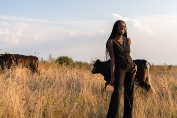 Happy smiling african girl in black clothes stands among the field, cows graze on the background