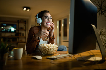 Young woman having fun while eating popcorn and watching movie on a computer in the evening.