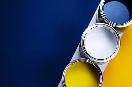 Cans of paint on a background of yellow and classic blue.