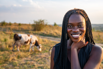 Close up portrait of the young african girl in black vest among the field, cow graze on the background