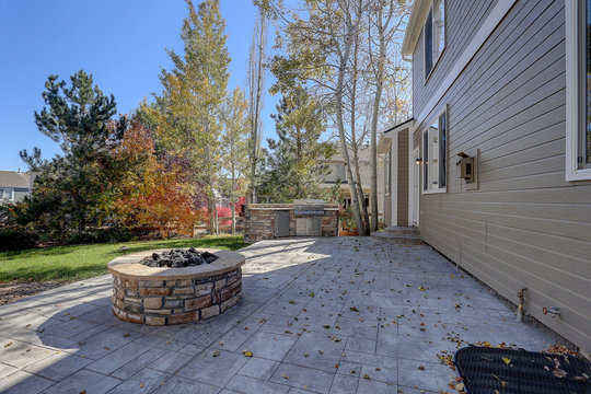 Back stone patio with fall trees and round stone firepit