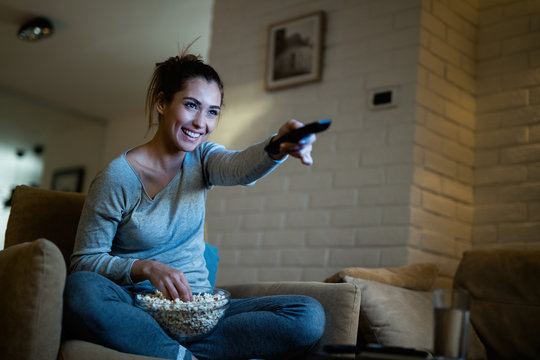 Happy woman using remote control while watching TV and eating popcorn at night.