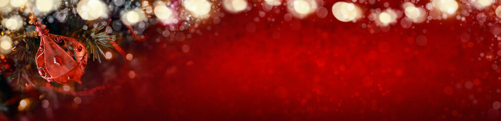 Red Christmas banner of tree decorations and glowing lights on a blurred festive background.