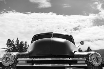 classic old American pickup car front low angle view, headlights light lamps and chrome view, during outdoor antique cars show, black and white