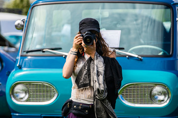 selective focus on young caucasian photographer woman holds DSLR camera in front of old blue van, wearing black hat scarf, during a antique cars show