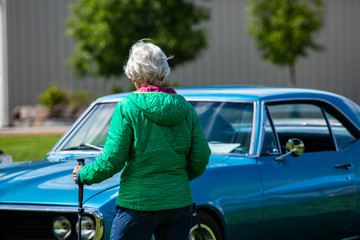 rear view of an old woman walking with hiking crutches, in front of classic muscle American blue car with opened hood during outdoor antique car show