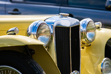 Old Classic antique car front details with cream white color and chrome body parts and big Headlamp lights and small lamps