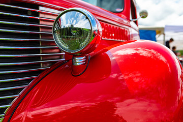 Old vintage American bright red pickup car front side close up view, with chrome glass headlights light lamp parts and grille during an outdoor show