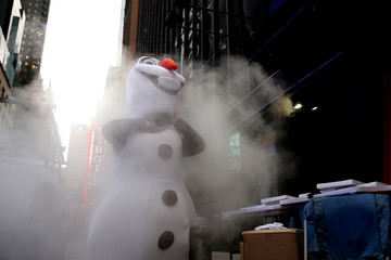 An performer playing Frozen character Olaf gets dressed at Times Square