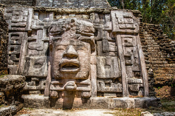 Old ancient stone Mayan pre-columbian civilization carved face and ornamen88t, Lamanai archeological site, Orange Walk District, Belize