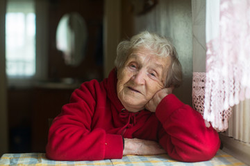 Portrait of old woman sitting at a table in the house.