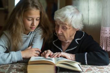 Little girl with her grandmother reading a book together.