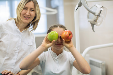 Dentist woman gives apple for smiling teenage girl in dental clinic.