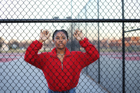A  portrait of a  beautiful black African-American teenaged girl posing outside by a black fence and looking sad