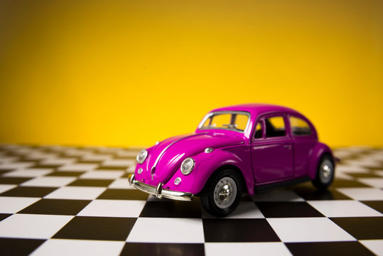 Pink beetle on a yellow background and checkered ground.