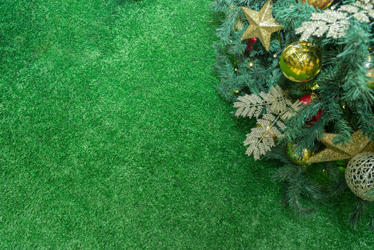 Close up of a green christmas tree decorated with colorful balls and leafs with a large green grass to text space. Focus selective. Copy space.