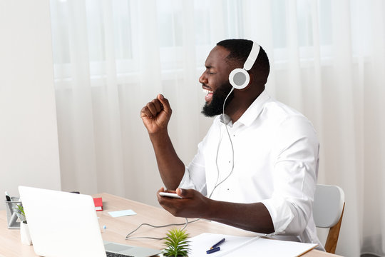 Emotional African-American man listening to music in office