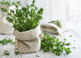 Fresh green thyme in decorative linen bag on an old wooden table.