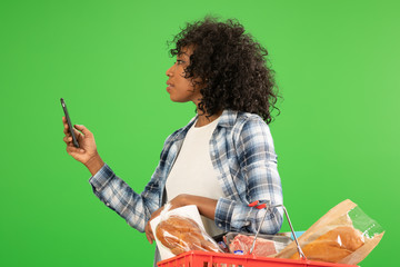 Side view of black woman with her phone grocery shopping on greenscreen