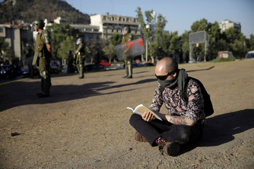 A protester reads a book as members of security forces stand during a protest against Chile's government in Santiago
