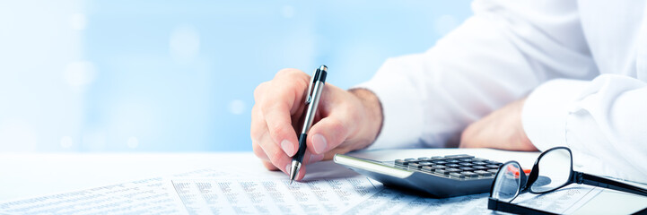 Business Man Using Pen And Calculator On Desk With Reading Glasses And Financial Report- Business...