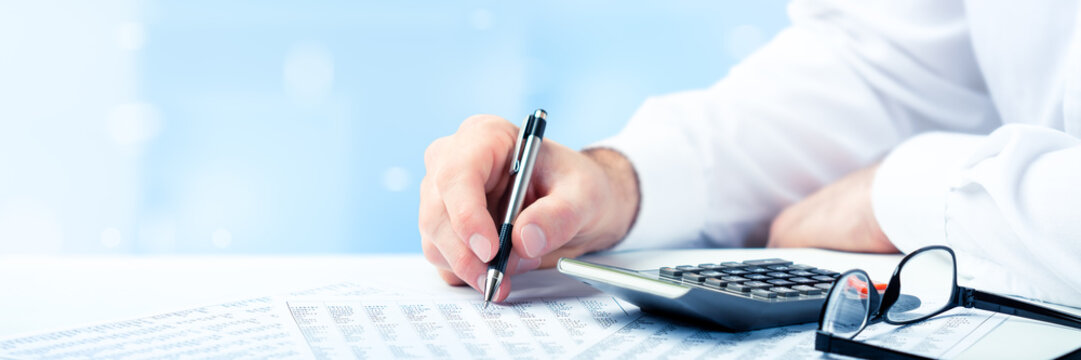 Business Man Using Pen And Calculator On Desk With Reading Glasses And Financial Report- Business Accounting Concept