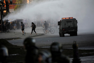 People run away as a water cannon is sprayed to disperse protesters during a protest against Chile's government in Santiago