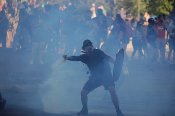 A protester throws back a canister of tear gas during a protest against Chile's government in Santiago