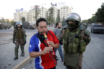 A member of security forces looks at a protester playing a flute during a protest against Chile's government in Santiago