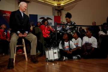 Democratic 2020 U.S. presidential candidate and former U.S. Vice President Joe Biden sits while kids from the Union Baptist Crusaders drill team look on during an event at the Brown Derby Ballroom in Waterloo, Iowa
