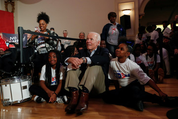 Democratic 2020 U.S. presidential candidate and former U.S. Vice President Joe Biden sits with kids from the Union Baptist Crusaders drill team during an event at the Brown Derby Ballroom in Waterloo
