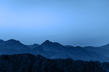 Beautiful dark blue mountain landscape with visible contrast on blue sky. Classic blue color of the year 2020.
