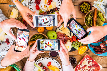 Group of unrecognizble friends or family caucasian people having fun together taking picure at their dishes with food - home or restaurant concept of people having fun with technology and media